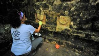 An archaeologist works cleaning the stucco of a temple in Kulubá, Yucatan state