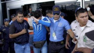 Policemen escort one of five Syrian men detained at Toncontin international airport in Tegucigalpa, Honduras on 18 November, 2015.