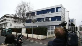 Cameramen film in front of the French far-right Front National (FN) headquarters in Nanterre, near Paris on 20 February 2017 during a search of the party's offices