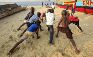 A group of young boys stretch their legs before playing a game of football on the beach