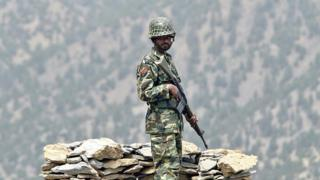 A Pakistani soldier stands guard in the mountain of Shawal along the Pakistan-Afghanistan border, 29 April 2006