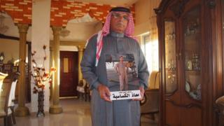 Safi Yousef al Kasasbeh holds a photograph of his son, Moaz
