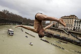 Marco Fois jumps from Cavour Bridge in front of a crowd.