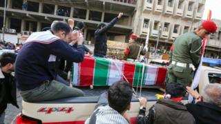 Mourners surround a car carrying the coffin of Iranian military commander Qasem Soleimani