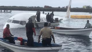 People in small boats around the plane in the water