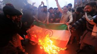 Men in Pakistan burn Indian flags after an Indian military incursion into Pakistani territory