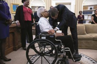 Obama kisses a women in a wheelchair