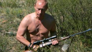 Vladimir Putin with a hunting rifle, pictured in 2007. The image is the July page on the 2018 Putin calendar.