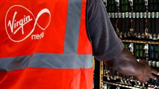 A Virgin media engineer - identified by the logo on the back of his high-viz vest - reaches across to touch the electrical innards of a telecoms cabinet