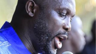 Close up of Mr Weah's face as he speaks into a microphone