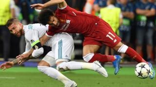 Mohamed Salah pugna con Ramos en la jugada en que se lesionó.