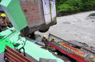 In this photograph taken on July 3, 2016, Indian State Disaster Response Force (SDRF)personnel examine the wreckage of a building after monsoon floodwaters devastated dwellings in the village of Ghat, near Karanprayag, Chamoli District in the northern state of Uttarakhand.