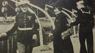 An image that looks strikingly similar to the infamous distracted boyfriend meme. An old photo in sepia colours from the 1950s. On the right, a male Navy cadet walks with his arm around a woman also dressed in Navy attire. She has her head turned and is reaching out to an impeccably-dressed man in Marine Corps dress blues. The man looks outrageously confident.