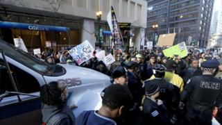Protesters hold signs calling for Rahm Emanuel to resign