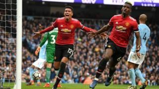 Paul Pogba (midig) iyo Chris Smalling ayaa dhaliyay goolasha ay Manchester United kaga badisay Man City