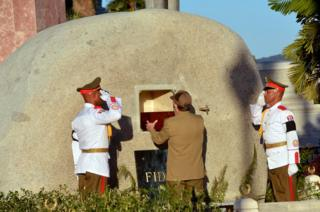 Cuba's President Raul Castro places the ashes of his older brother Fidel Castro into a niche in his tomb