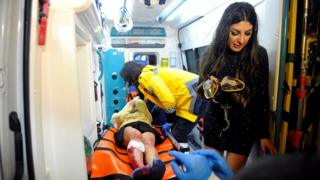 An injured woman is carried to an ambulance from a nightclub where a gun attack took place during a New Year party in Istanbul