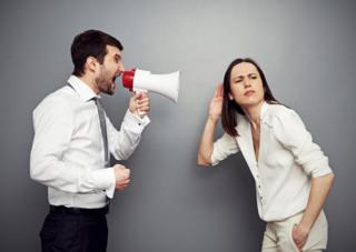 Imagem mostra homem com um megafone tentando se fazer ouvir por mulher