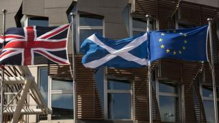 A Scottish Saltire (C) flies between a Union flag (L) and a European Union (EU) flag in front of the Scottish Parliament building in Edinburgh