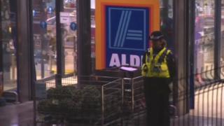 A policewoman outside the Aldi