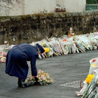 Queen Elizabeth II laying a wreath at the gates of Dunblane Primary School after one of the deadliest firearms incidents in UK history.