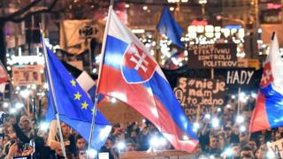 """A Slovak flag is held aloft at a rally near the Slovak National Uprising square against corruption and to pay tribute to murdered Slovak journalist Jan Kuciak under the slogan """"For a Decent Slovakia"""", on March 16, 2018 in Bratislava, Slovakia"""
