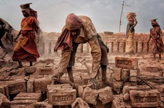 A man bends over picking up bricks as women work behind him