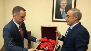 مسؤول بالخارجية السورية يعطي الوسام لمسؤول من السفارة الرومانية في دمشق
