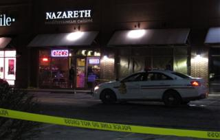 A police car parked outside the restaurant where the machete attack happened
