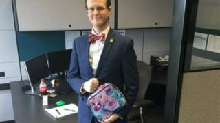 photo shows David Pendragon wearing a suit in an office and holding a lunchbox with pictures of cats on it.