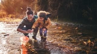 父亲教儿子在山溪里捉鱼