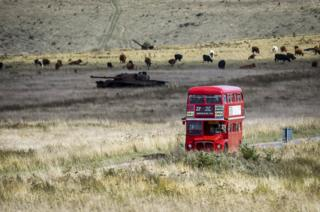 A routemaster bus passing a destroyed tank as it makes its way from the deserted village of Imber on Salisbury Plain