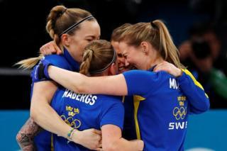 Team Sweden hug each other in celebration