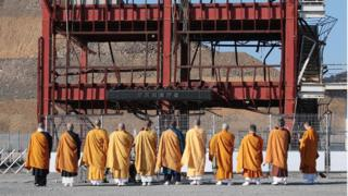 Buddhist monks pray for victims of the massive earthquake and tsunami disaster which hit northeastern Japan in 2011 in front of former municipal disaster prevention centre building in the town of Minamisanriku, Miyagi prefecture on March 11, 2016