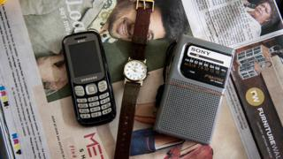 A mobile phone, a watch and a radio transmitter lying on a newspaper in a room at the care home