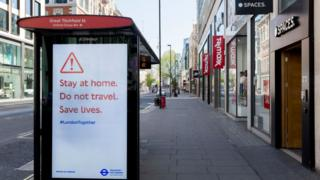 Deserted Oxford Street in London, and a bus shelter sign warning shoppers to stay home