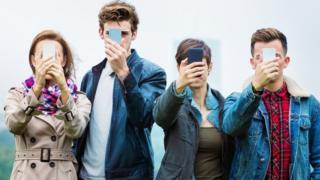 Cuatro personas jóvenes sostienen teléfonos inteligentes frente a sus caras