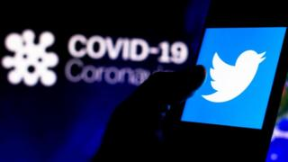 Twitter logo seen on a smartphone with a computer model of the coronavirus in the background.