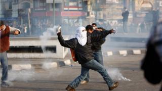 治安部隊が使用した催涙ガスの缶を投げ返すデモ参加者(2011年1月、エジプト・カイロ)