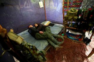 A couple from the 51st Front of the Revolutionary Armed Forces of Colombia (FARC) rest inside a tent at a camp in Cordillera Oriental, Colombia,