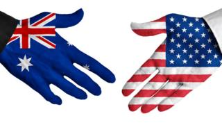 A stock image of a hand painted with an Australian flag reaching out to hand with an American flag