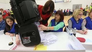 Electoral staff empty a ballot box for counting