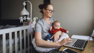 Woman in front of a computer with a baby on her lap
