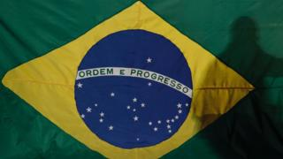 Sombra de um homem em frente a bandeira do Brasil exposta em manifestação