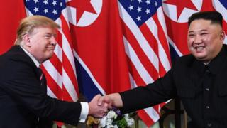 US President Donald Trump (L) shakes hands with North Korea's leader Kim Jong Un