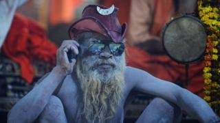 An Indian sadhu (Hindu holy man) sits inside his tent as he use his mobile phone during the Kumbh Mela festival area in Allahabad on January 13, 2019