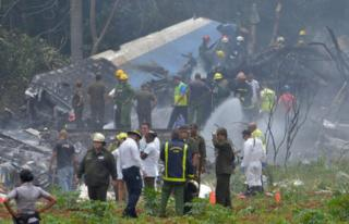 A picture taken at the scene of the accident shows charred portions of the plane and emergency workers
