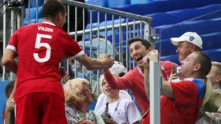 Игрок сборной России Виктор Васин (слева) общается с болельщиками после победы в матче
