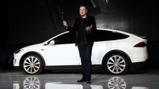 Elon Musk speaks in front of a Tesla SUV