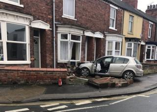 Car crashed into front of a house with wall rubble surrounding the vehicle